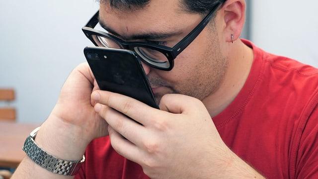 Ein Mann mit Sehbehinderung hält sein Smartphone nahe ans Gesicht.