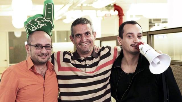Die Regisseure mit einem Protagonisten. ein Regisseur hält ein Megaphon vor dem Mund und der Protagonist hat einen grossen grünen Pappzeigefinger an der Hand