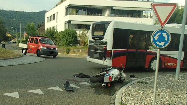 """Töff liegt am Boden neben einem Schild """"Kein Vortritt"""". Daneben der Linienbus."""