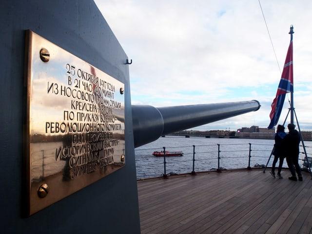 Das Kriegsschiff Aurora mit einer goldenen Aufschrift. Auf dem heutigen Museumsschiff stehen zwei Touristen.
