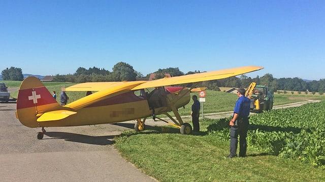 Ein gelb-rotes Kleinflugzeug steht halb auf Strasse, halb auf Wiese