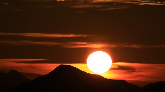 Die Sonne geht über eine dunklen Berg auf.