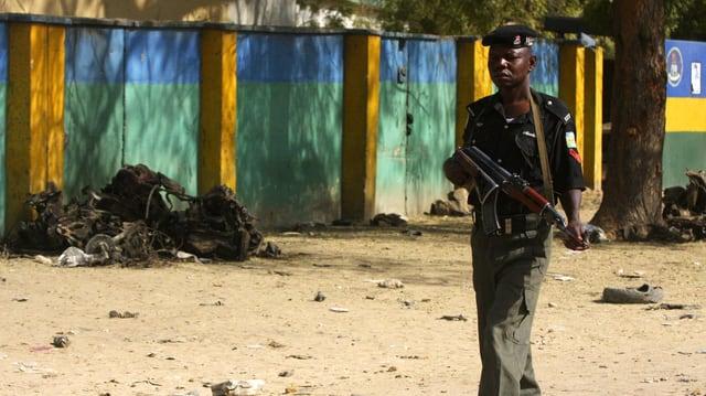 Afrikanischer Polizist in Kano vor Trümmern eines Anschlags.