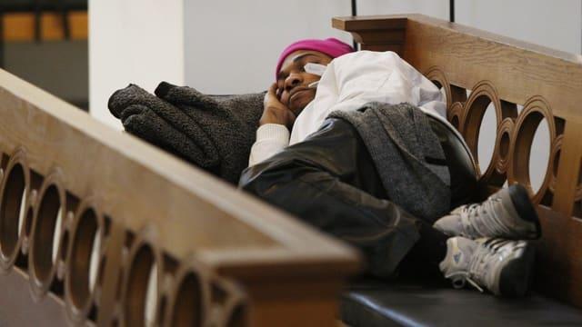 Ein Flüchtling ohne Papiere schläft auf einer Kirchenbank