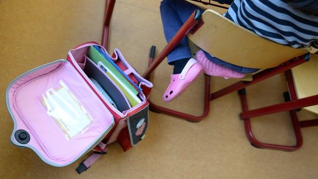 Offener Schulsack neben Pult.