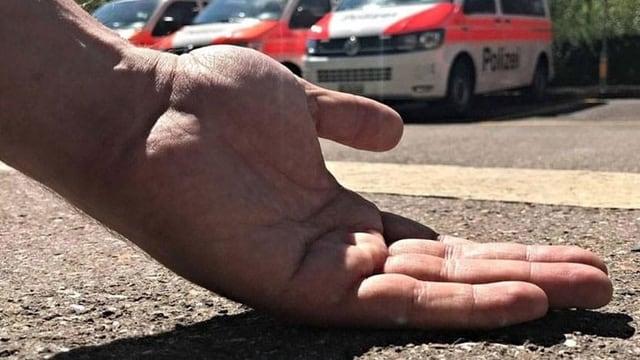 Hand mit Handrücken auf dem Asphalt.