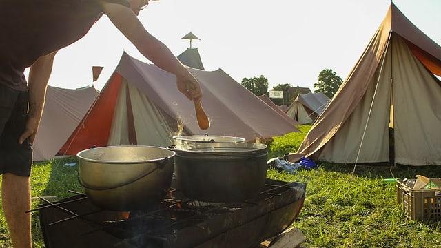 Drei Kochkessel auf eine Gitter über einer aufgeschnittenen Blechtonne, die als Feuerstelle dient. Im Hintergrund Spatzzelte