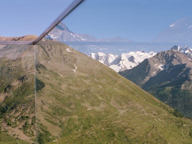 Eine Berglandschaft, davor ein Absperrglas, das mit Metallstreben in vier Teile geteilt wird.