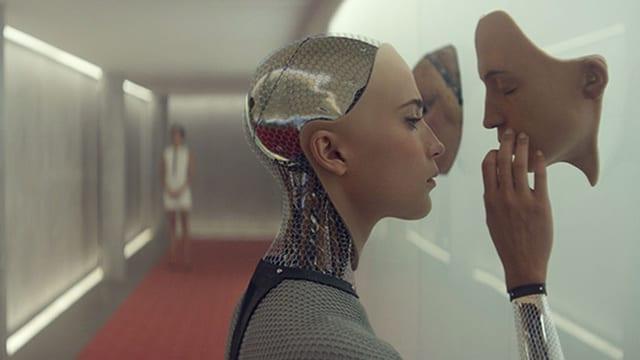 Ein weiblich gestalteter Roboter berührt eine Maske an der Wand.