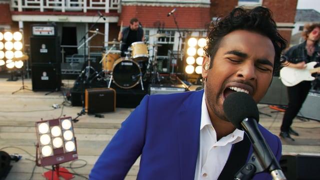 Eine Band spielt auf einer Bühne, im Vordergrund ein Mann, der in ein Mikrofon singt.