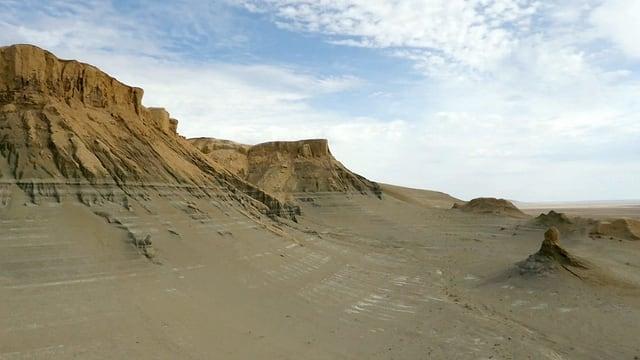 Eine Landschaftsaufnahme der Atacama-Wüste in Südamerika zeigt eine braun-sandige Ebene und Felsen im Hintergrund.