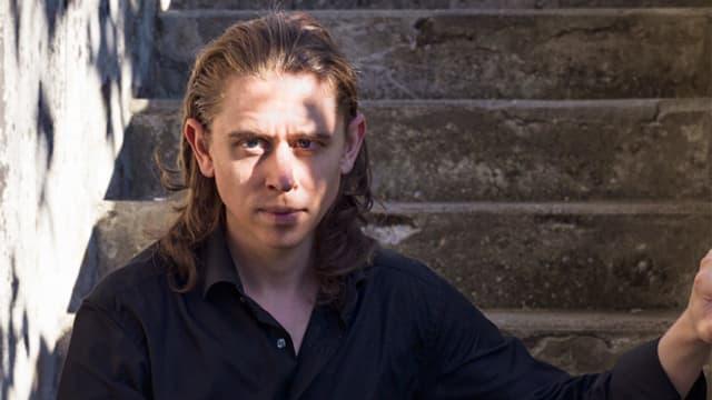Ein junger Mann sitzt auf einer Steintreppe.
