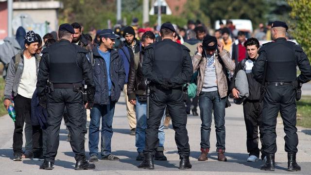 Männer stehen auf einer Strasse drei Polizisten gegenüber.