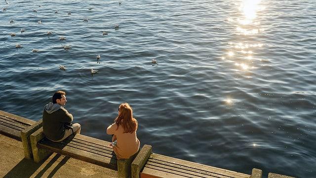 Ein Mann und eine Frau sitzen am Ufer eines Sees