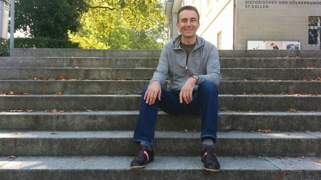 Hansruedi Nef sitzt im grauen Pullover und blauen Jeans auf einer Treppe in der Innenstadt von St. Gallen.
