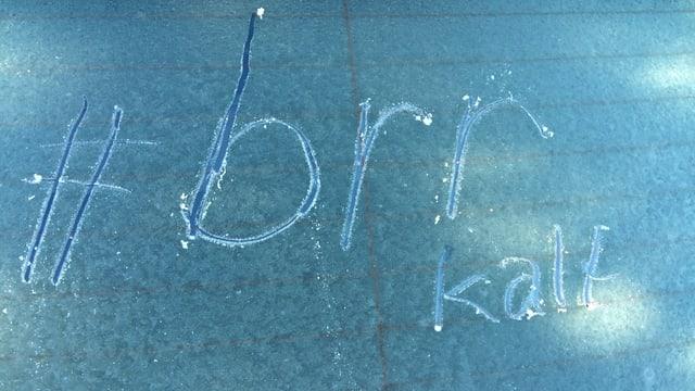 Nieseltröpfchen verhüllen Autoscheibe unter einer dünnen Eisschicht.