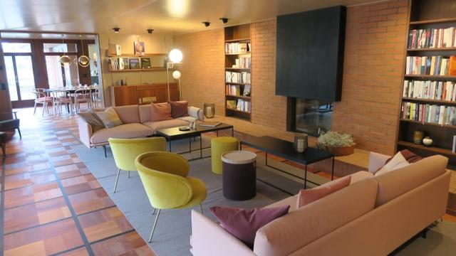 Wohnzimmer mit pastellfarbenen Sitzgruppen, Cheminée und Büchergestellen.