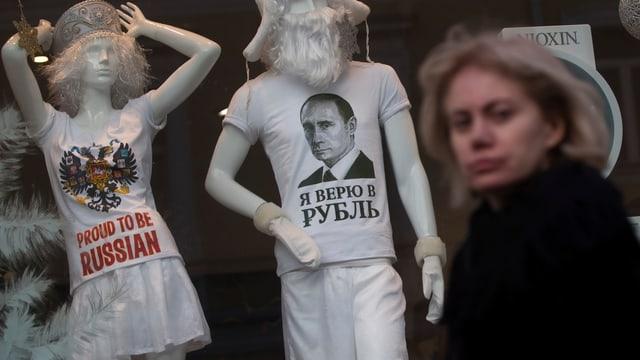 Frau vor einem Schaufenster, zwei Schaufensterpuppen mit «proud to be russian»-Shirts.