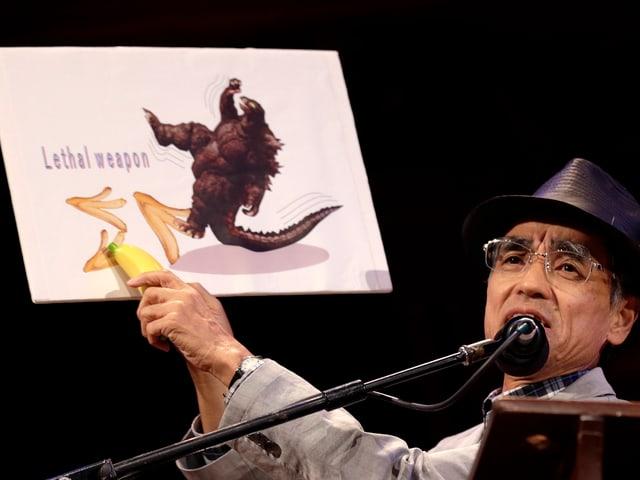 Ein japanischer Forscher mit einem Schild zur Gleitfähigkeit von Bananenschalen.