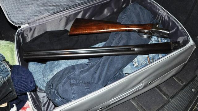 Eine Schrotflinte liegt in zwei Teilen in einem Koffer mit Kleidern