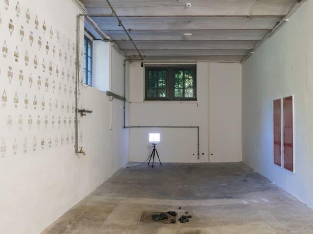 Kellerraum mit weissen Wänden, Wandbild und Baulampe.