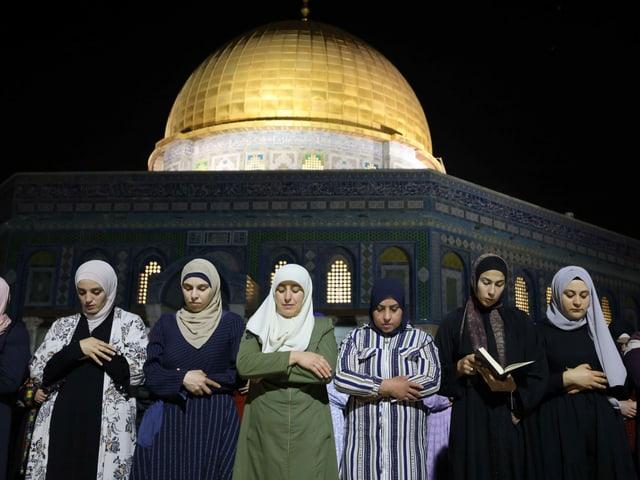 Palästinenserinnen beten vor einer Moschee.