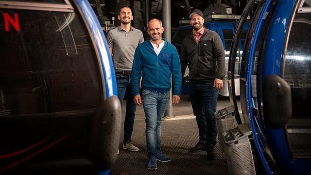 Die drei Herren der AG vor mehreren Kabinen der Bergbahn.