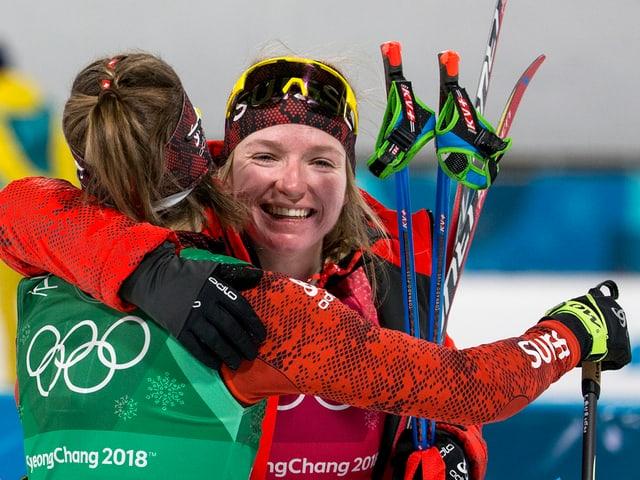Nadine Fähndrich umarmt eine andere Langläuferin.