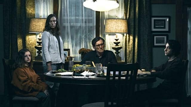 Eine Familie sitzt in einem düsteren Wohnzimmer um den Tisch