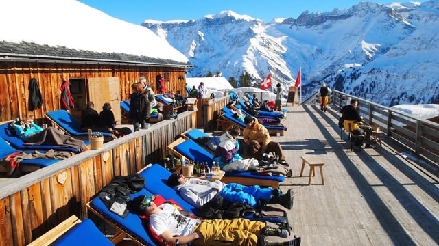 Skifahrer liegen auf Liegestühlen auf einer Sonnenterrasse