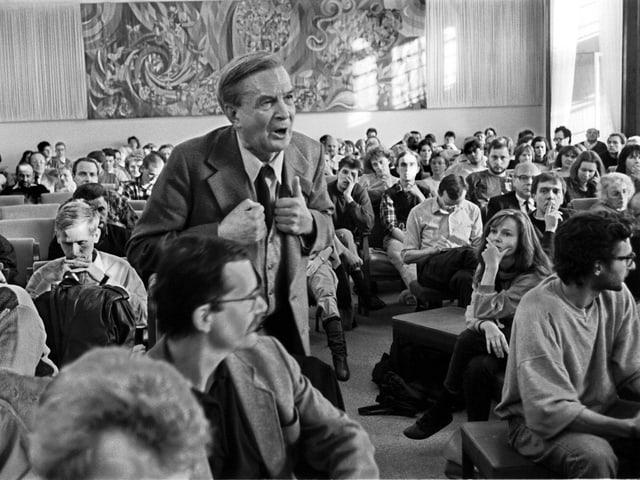 Dr. Friethjoff Sielaff inmitten von Zuhörern, man sieht, dass er energisch argumentiert.