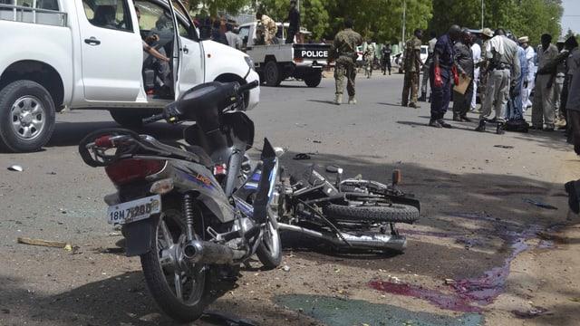 Blut ist auf der Strasse. Sicherheitskräfte untersuchen den Tatort.