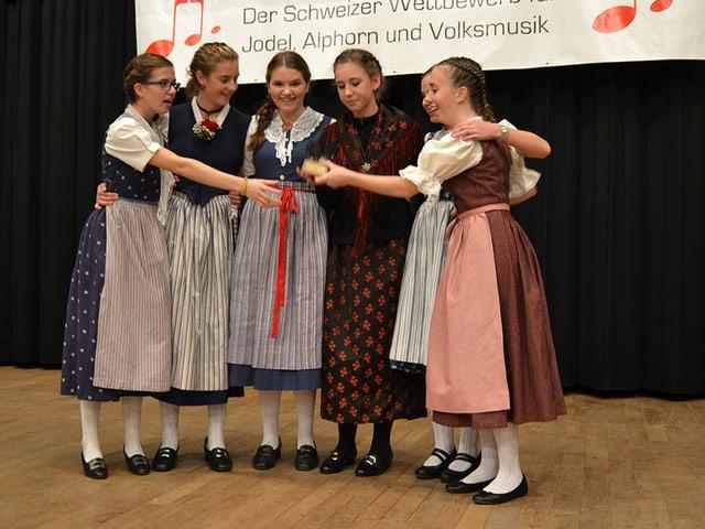 Sechs Mädchen freuen sich auf der Bühne.