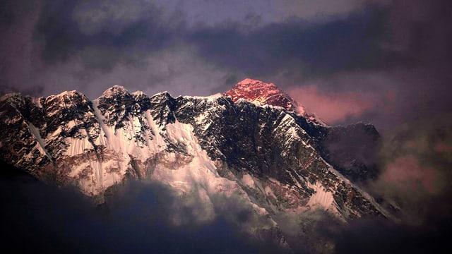 Mount Everest leuchtet im Abendrot hinter einer Gebirgskette.