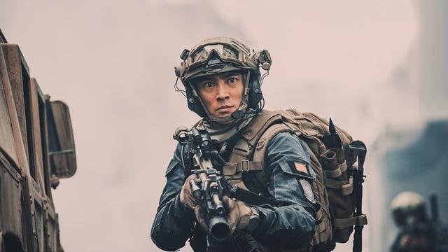Ein chinesischer Soldat schaut schwer bewaffnet in die Kamera.