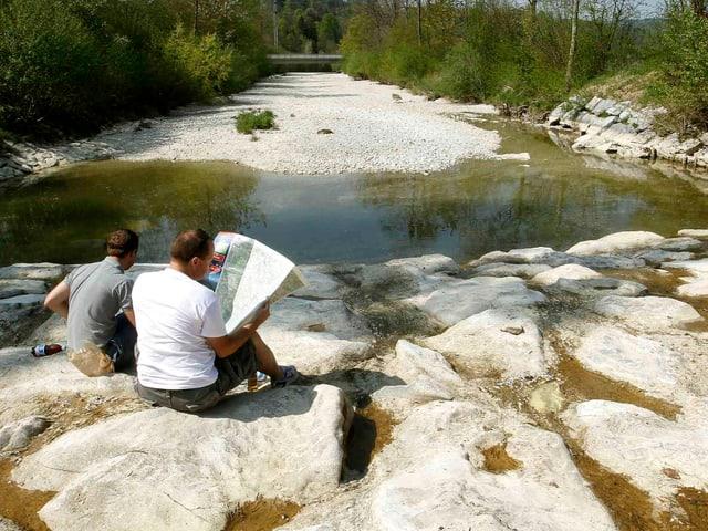 Zwei Männer sitzen auf grossen Steinen im fast trockenen Flussbett der Töss. In einer Senke des Flussbettes hat es stehendes, braunes Wasser.