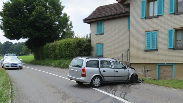Silbernes Fahrzeug mit eingedrückter Front steht quer in einer leichten Kurve, die Nase an einer Hauswand.