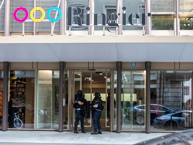 Zwei Polizisten sichern den Eingang des Ringier-Verlagshauses.