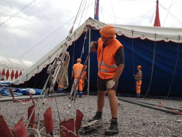 Ein Mann mit oranger Weste bedient einen Metallhebel.