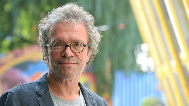 Porträt von Sandro Lunin: Ein Mann mit grauem, gelockten Haar und Brille. Er steht vor einem bunten Hintergrund.