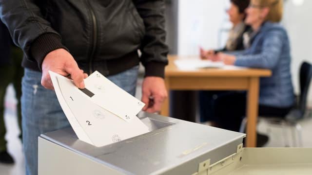 Mann wirft Stimmzettel in Urne