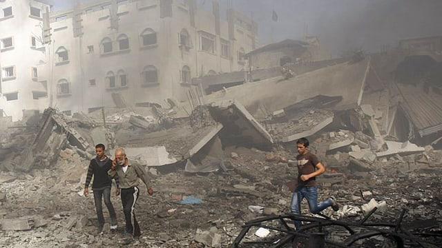 Drei Menschen flüchten, sie rennen durch Trümmerhaufen.