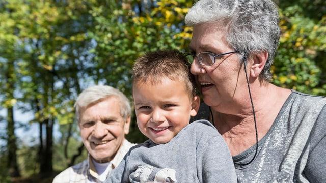 Lachende Grosseltern mit ihrem Enkelsohn.