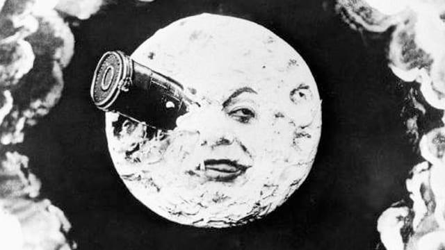Schwarz-Weiss-Bild: Ein Mond mit einem Gesicht. Ein Auge ist von einem Fernrohr bedeckt.