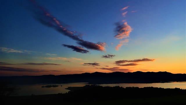 Blick vom Etzel zum Seedamm, darüber ein tiefblauer Himmel und dahinter ein zartes Morgenrot über dem Zürcher Oberland.