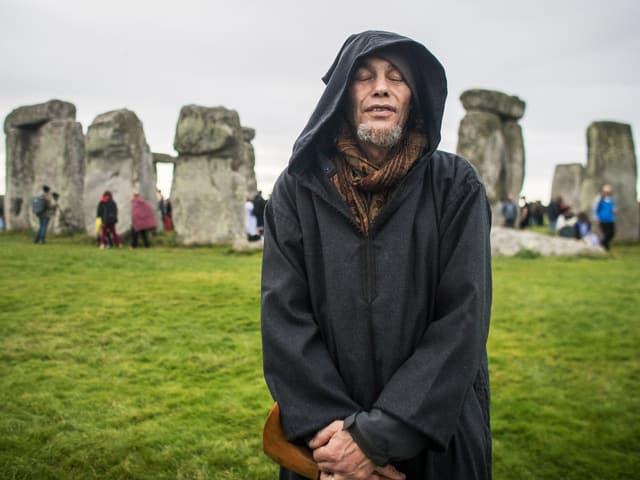 Mann in schwarzem Umhang mit Kapuze steht mit geschlossenen Augen vor Steinkreis