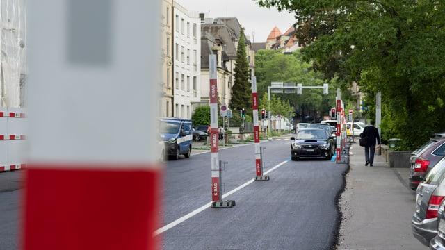 Frisch ausgebrachter Asphalt auf einer Strasse, Bauabschrankungen, parkierte Autos