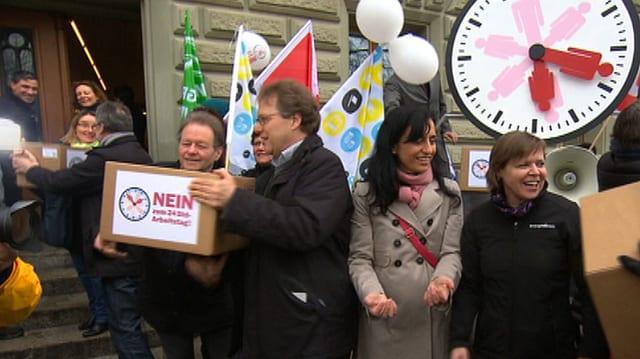 Vertreter der Sonntagsallianz tragen gemeinsam Schachteln mit Unterschriften in die Bundeskanzlei.