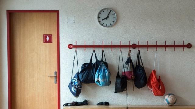Bank mit Turnsäcken vor einer Mädchentoilette in einem Schulhaus.