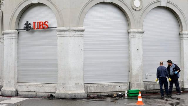 Zwei Arbeiter vor einer geschlossenen UBS-Filiale.